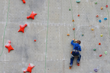 Back of boy climbing with rope on special wall for climbing