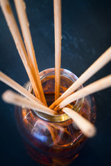 Macro shot of sticks in aroma reed diffuser. Toned image.
