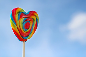 Bright rainbow lollipop on stick and blue sky at summer