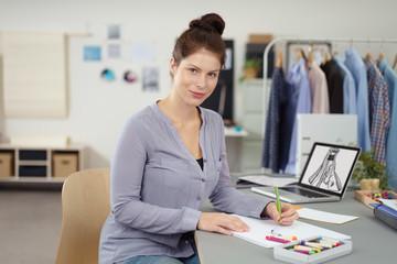 designerin arbeitet an einem entwurf für ein kleid