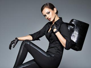 Portrait of beautiful woman in black holding handbag