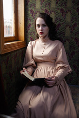 Young woman in beige vintage dress of early 20th century reading
