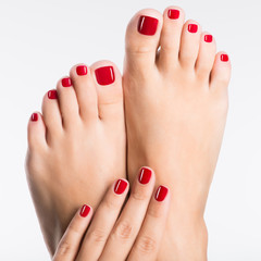 Wall Murals Pedicure Closeup photo of a female feet with beautiful red pedicure
