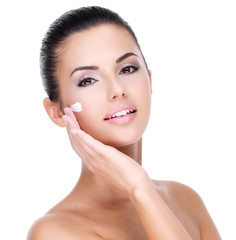 Fototapete - Young woman with cosmetic cream on face