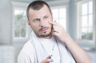 Man checking his wrinkles in bathroom