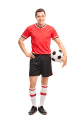 Young soccer player holding a ball and posing