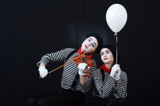 a guy and a girl mimes playing the violin