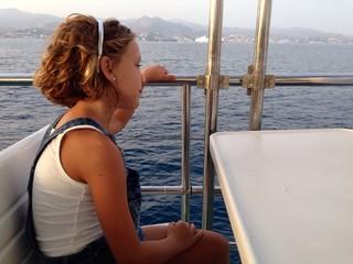 niña rubia en un barco navegando por la costa de malaga