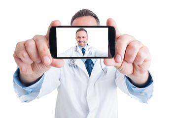 Handsome doctor or medic taking a selfie with back camera
