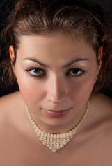 Portrait of a brunette with a necklace of beads closeup