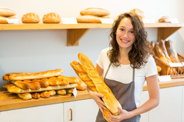 Young attarctive baker working at the bakery