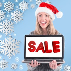 Composite image of festive blonde holding a laptop