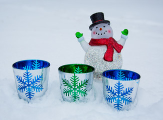 Smiling glass snowman decoration in the snow with colorful glass snowflake decorations.