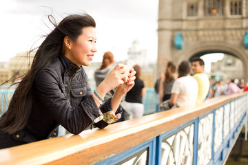 japanese woman taking a photo with her mobile phone from tower bridge