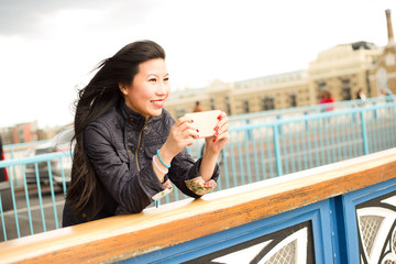 Japanese girl taking a photo from tower bridge