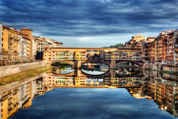 Tuinposter Florence Ponte Vecchio bridge in Florence, Italy. Arno River under dark, stormy clouds.