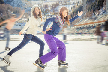 Group funny teenagers ice skating outdoor at ice rink