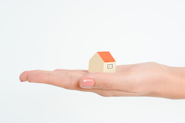 Close-up of woman's hands holding a small model house