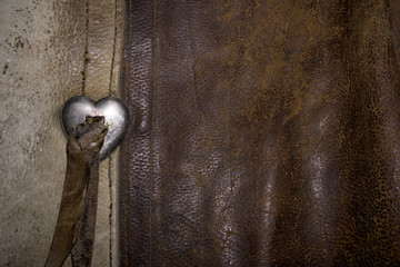 A close up photo of a pair of worn leather cowgirl chaps.  The rich brown colors of the leather and the silver heart would make a nice background for a western theme.