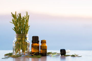 Rosemary aromatherapy essential oils in bottles on sunset