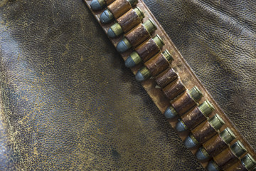 Western gun belt and bullets on a rich brown, worn leather background.