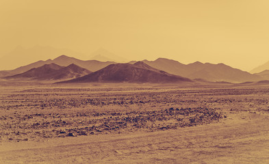 African desert, sandstorm and stone hills on a horizon.