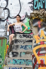 Portrait of thai adult beautiful girl relax and smile on graffiti wall