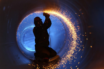 A worker works inside a pipe on a pipeline construction