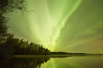 Northern lights (Aurora Borealis) glowing in the night sky over a beautiful lake in Finland. Vibrant colors on the sky and reflections on the still water of the lake.