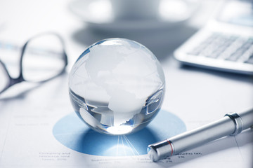 glass globe with stock charts and calculator