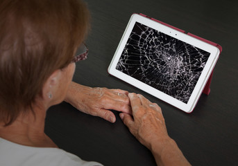 Senior lady with tablet, cracked screen