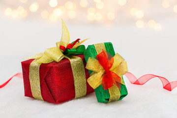 Red and green Christmas gift box with shiny ribbon. Bokeh with glow effect on white background
