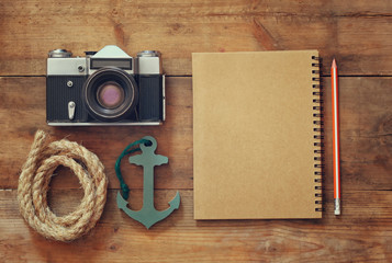 top view image of blank notebook, nautical rope, anchor and camera. travel and adventure concept. retro filtered image