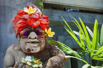 Humorous face portrait of old traditional Balinese temple guard statue dressed in funny tourist costume with sunglasses Arts, culture of Bali and Indonesian people and asian vacation travel background