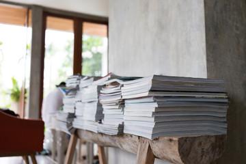 stack of magazine books on wooden table shelf in living room