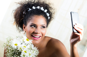 Portrait of beautiful exotic emotional bride taking a selfie