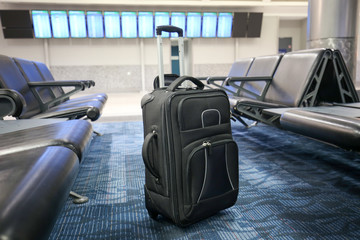 Black suitcase is left or lost at an airport hall.