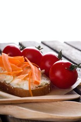 Bread with cheese and carrot on wooden board