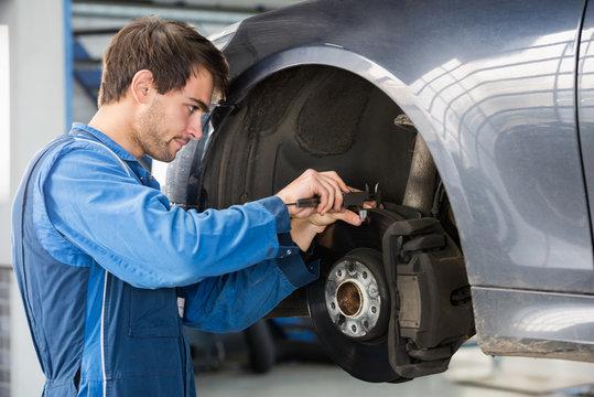 Car Mechanic Examining Brake Disc With Caliper