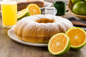 Orange cake on the table with fruits and juice.