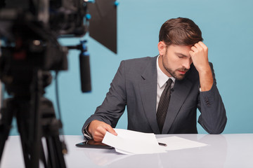 Handsome male newscaster is suffering from headache