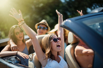 young people having fun in a black convertible by a sunny day