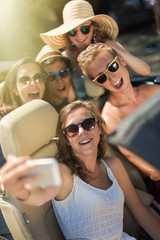 young people taking selfies with a smartphone in convertible