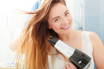 long haired woman drying hair in bathroom