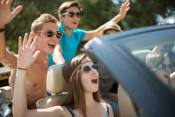 Young people having fun in the summer on a black convertible.