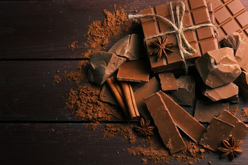 Fototapete - Black chocolate pieces with spices on wooden background
