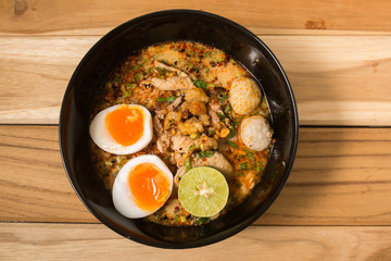 bowl of noodles with vegetables and soft boiled egg on wooden ta