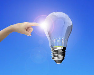 Human forefinger touching lightbulb with wind turbines inside