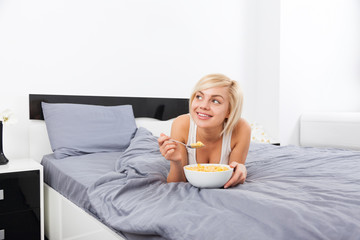 Breakfast in bed, young woman lying on bed