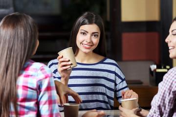 Beautiful girls speaking in cafe